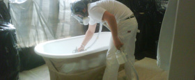 A bathtub Refinisher working on a claw foot tub